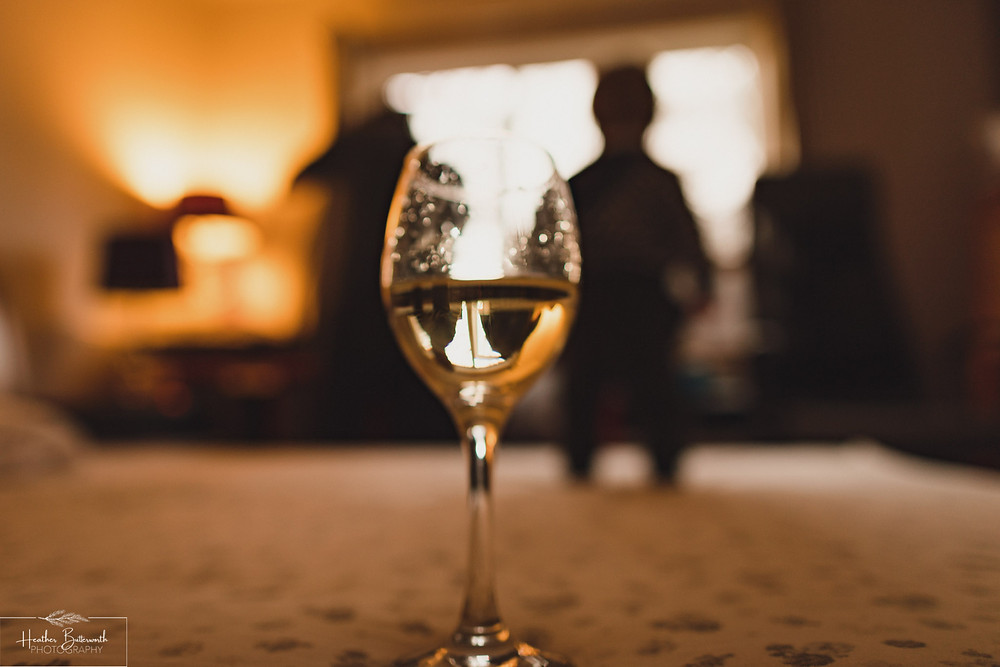 glass of white wine on the bed with a reflection of a dad and a toddler dancing in the light together behind it