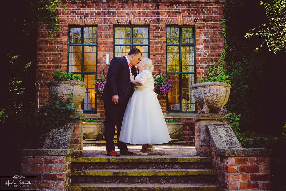 Bride and groom kissing outside after their wedding at Aldwark Manor Hotel and Spa in York, Yorkshire