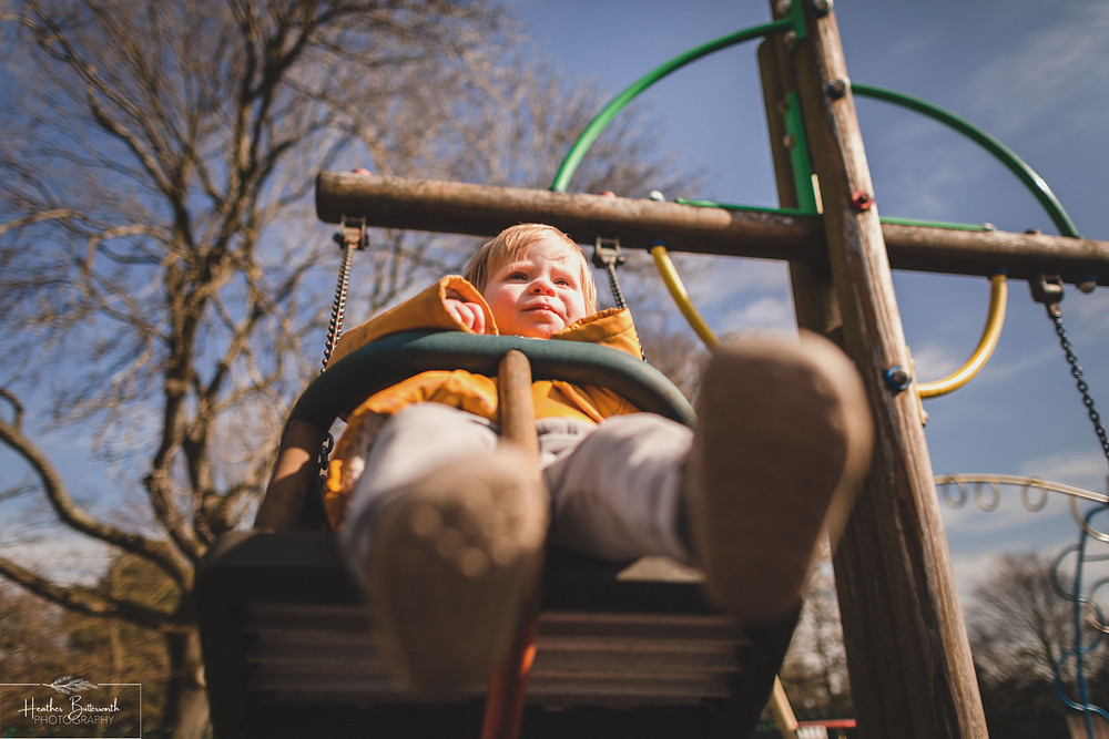 toddler on a swing in a playground from an interesting angle