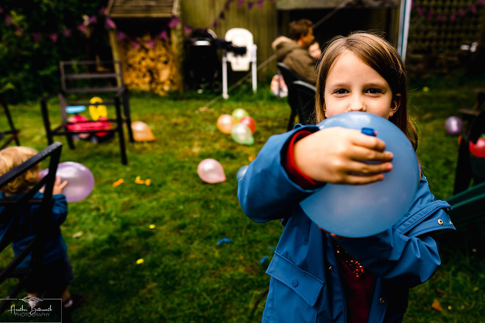 girl playing with a balloon in a garden in leeds yorkshire in july 2020