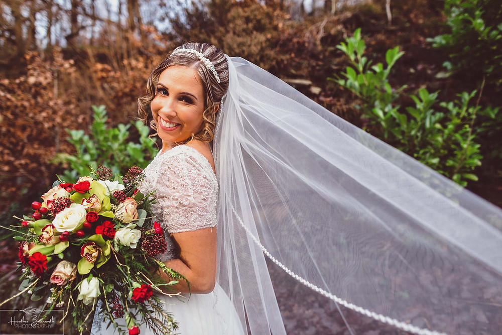 A smiling bride with her veil after her wedding at The Woodman Inn in Thunderbridge near Leeds, Yorkshire