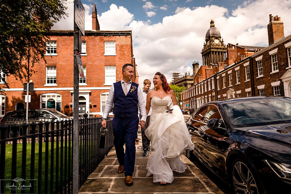 bride and groom walking with family after their wedding ceremony at Leeds Town Hall in August 2020