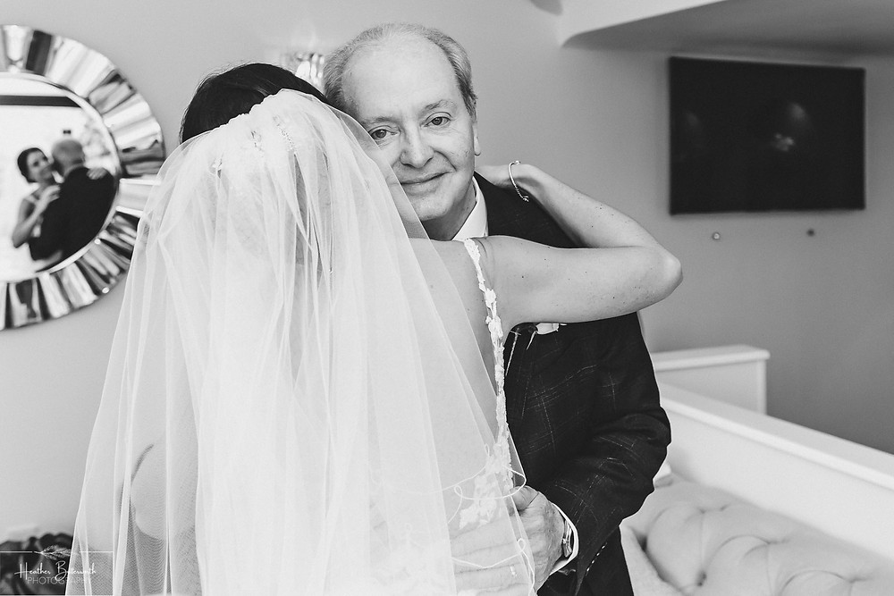 Father of the bride hugging his daughter with their reflection in a round mirror during bridal preparations at The Burnside Hotel and Spa in Bowness-on-Windermere