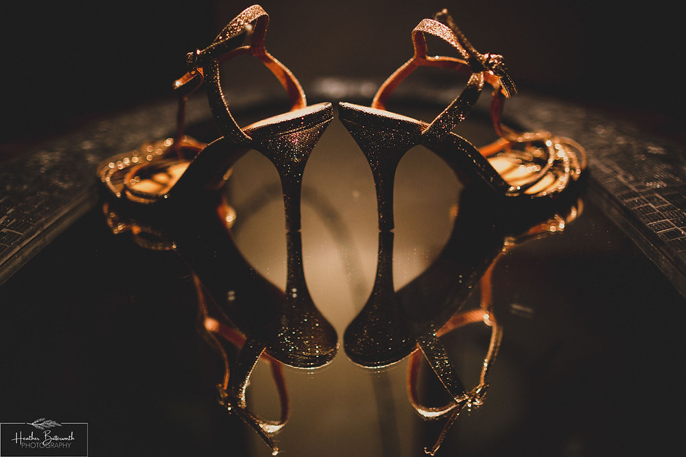 Gold glittering shoes photographed with a warm light on them on a mirror