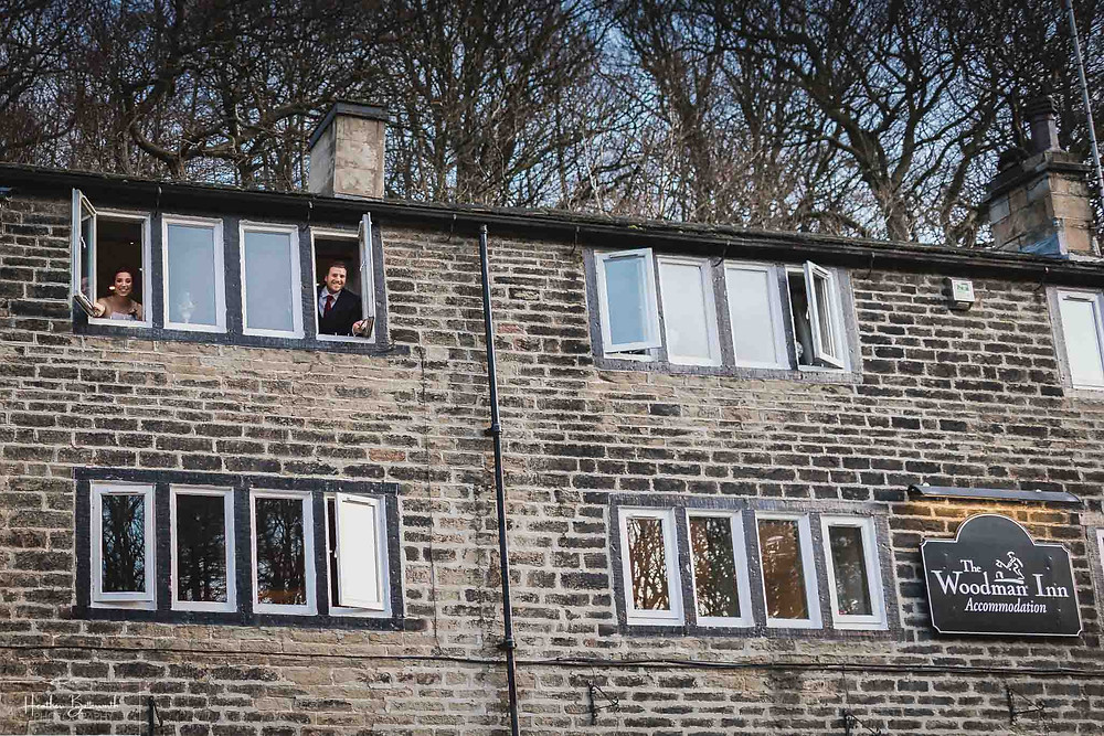 family at the bedroom window after the wedding at the woodman inn Yorkshire leeds photographer