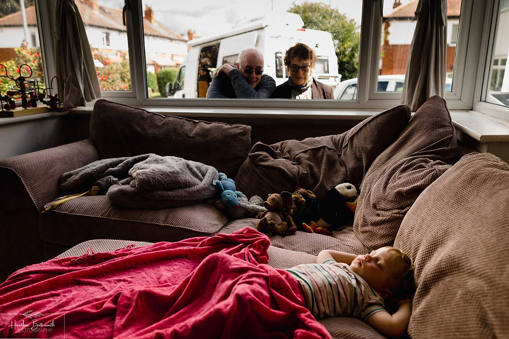 grandparents looking through the window at their grandchild during social distancing in june 2020 in leeds yorkshire