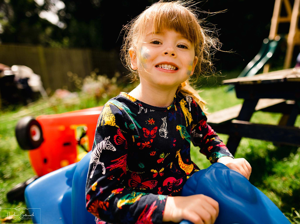 little girl smiling and playing in a garden