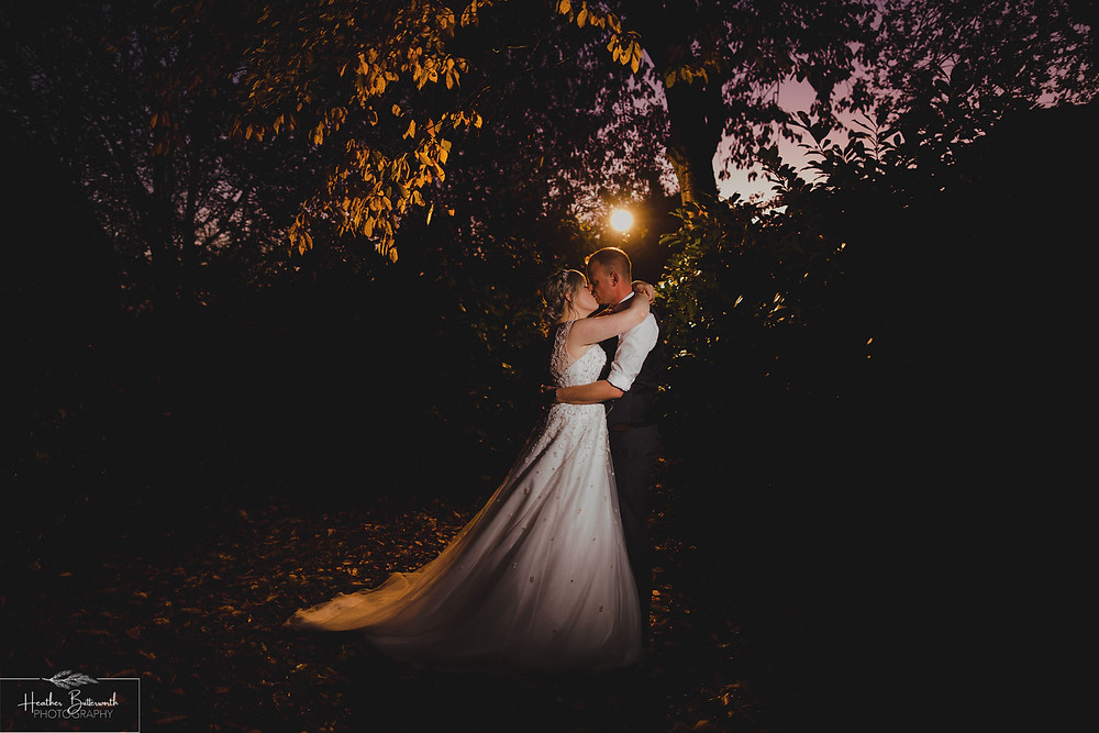 Bride and groom kissing in the grounds at their wedding reception after their wedding at Adel Parish Church in Leeds, Yorkshire