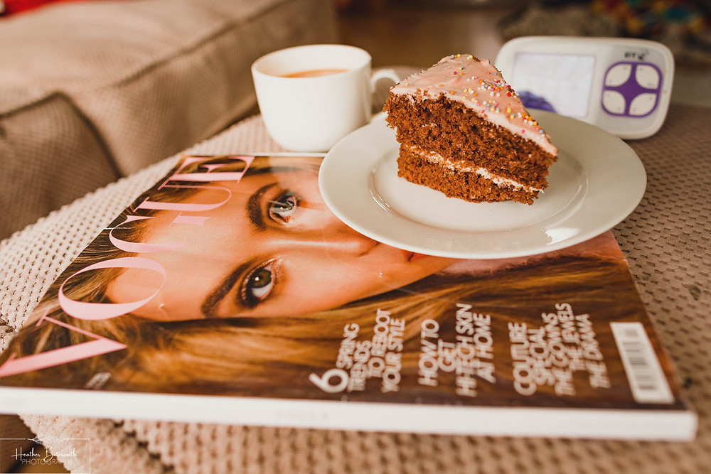 chocolate cake with a cup of tea and a copy of vogue with a baby monitor behind