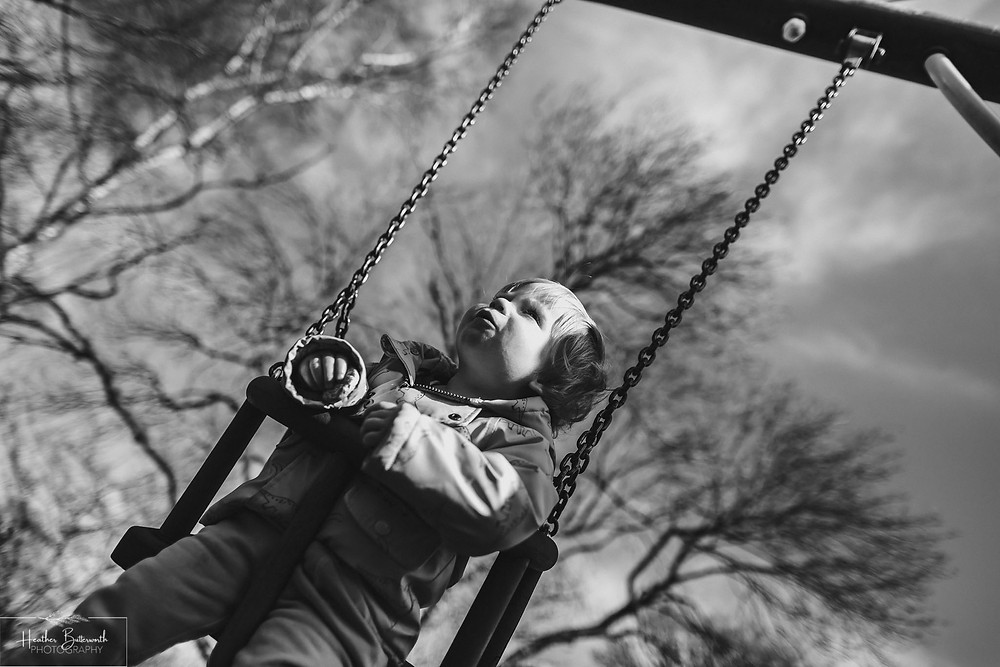 toddler on a swing in a playground with the light on his face