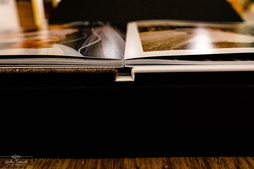 spine view of a wedding album on a wooden table by Heather Butterworth photography