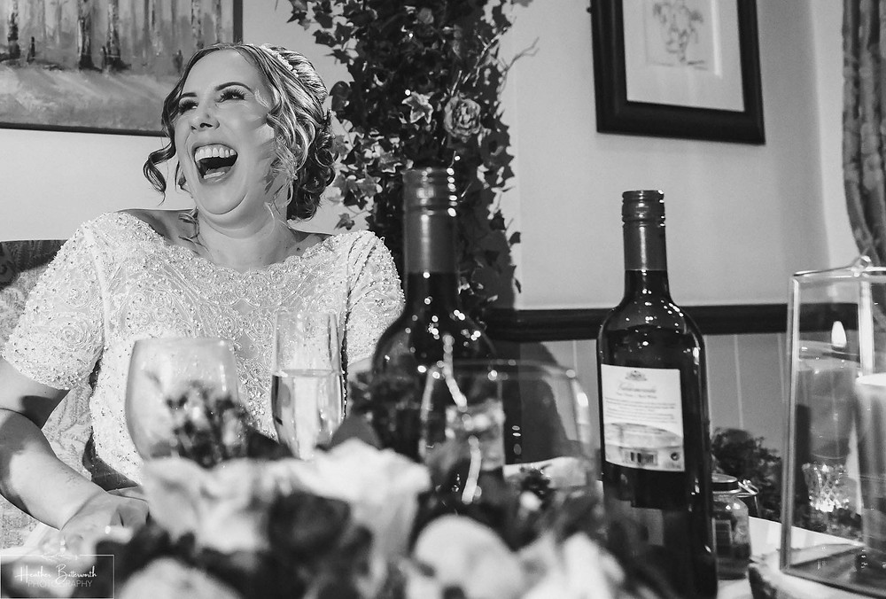 Bride laughing during the Grooms speech at The Woodman Inn in Thunderbridge, Yorkshire
