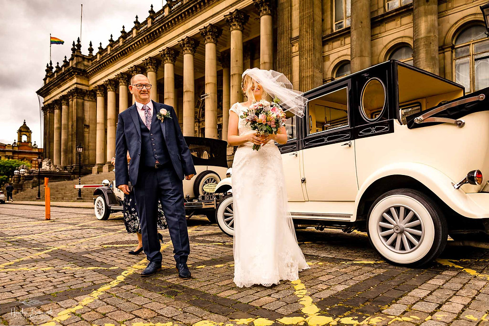 bride and her father outside the vintage car they arrived in at Leeds Town Hall before her wedding in Leeds Yorkshire UK in august 2020