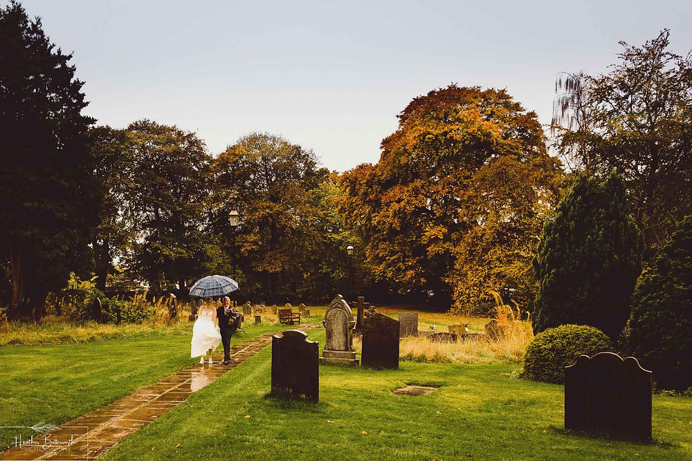 Bride arriving with her dad in the rain with an umbrella for the wedding at Adel Parish Church in Leeds, Yorkshire