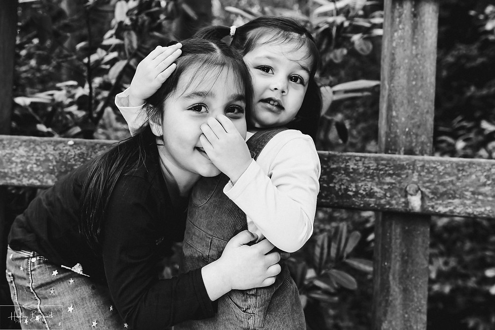 black and white image two young sisters hugging with a toddler grabbing her sisters nose in a wood.