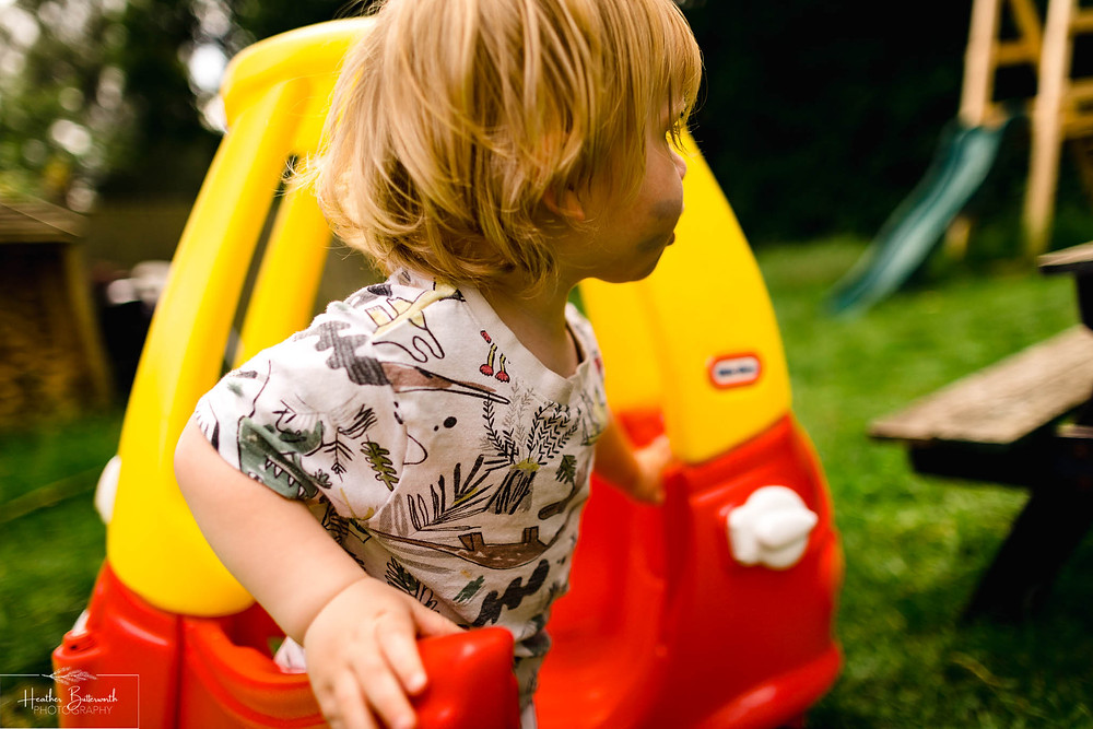 little boy playing in a toy car