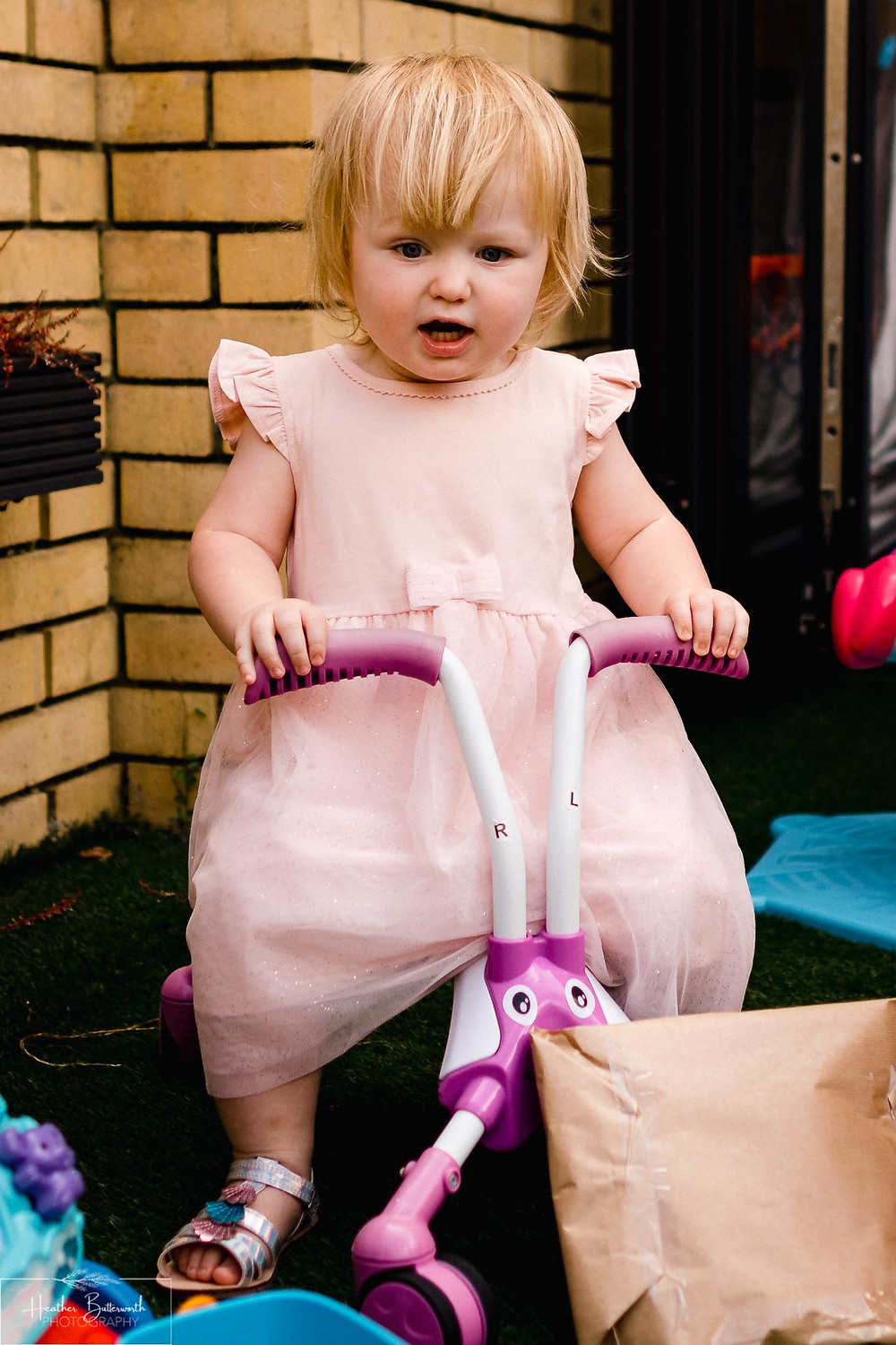 little girl in her new dress on her new bike playing happily