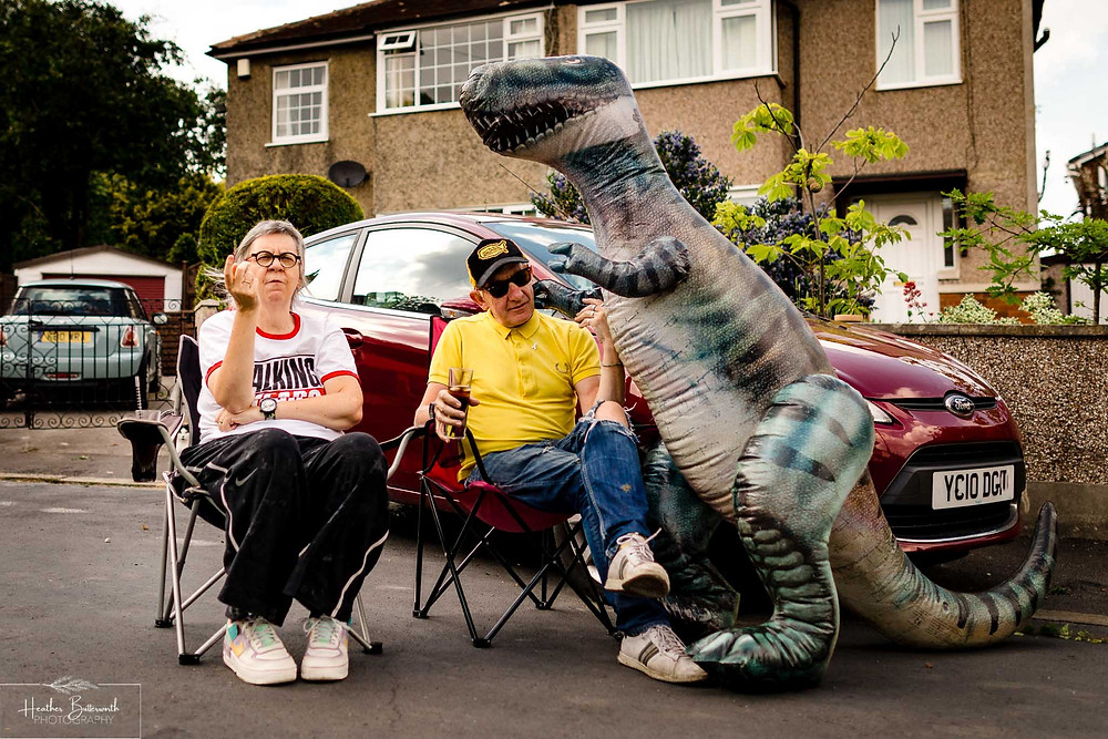 couple sitting in the street with an inflatable dinosaur together after restrictions were slightly lifted after the COVID-19 lockdown in Leeds , Yorkshire in June 2020