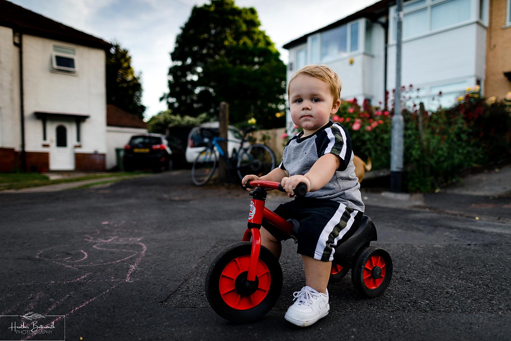 toddler in the street on a small bike