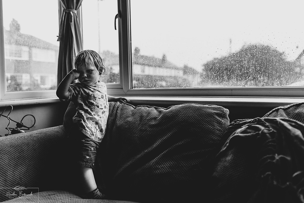 child stood in the window looking soaked after flying outside in the rain in Leeds Yorkshire UK in July 2020