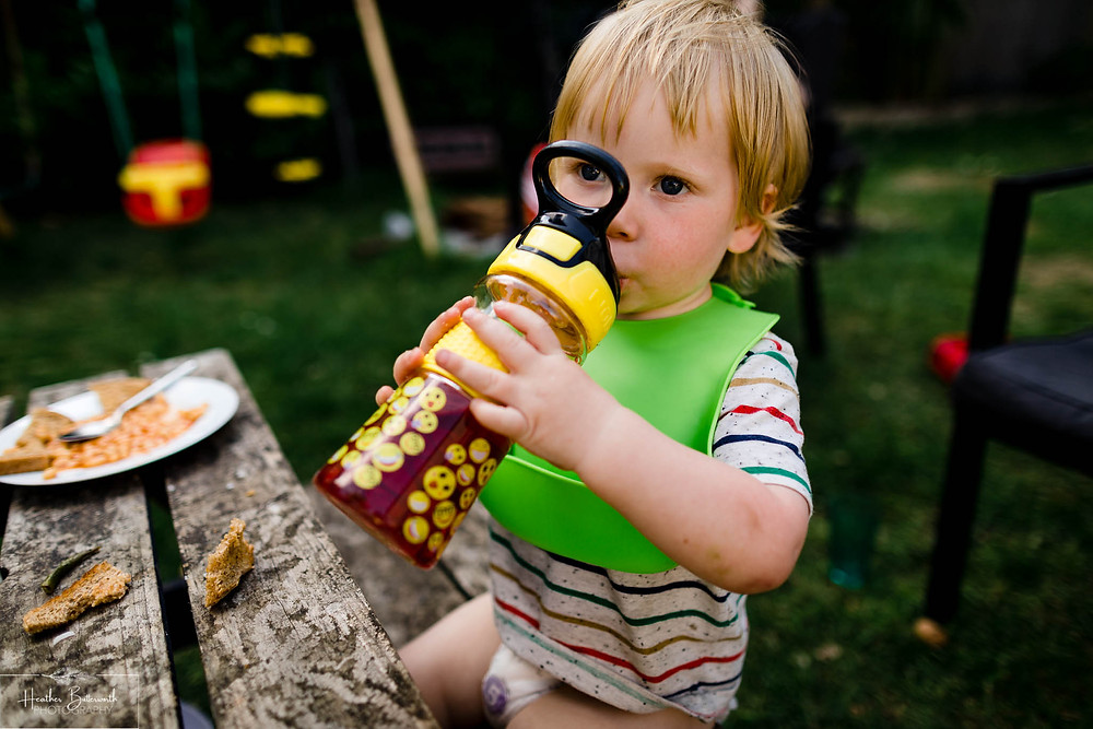 toddler drinking a purple drink from a bottle in the garden