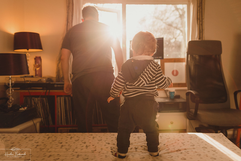 Dad DJing with his toddler son dancing behind him on the bed as the sun streams through the window in front of them