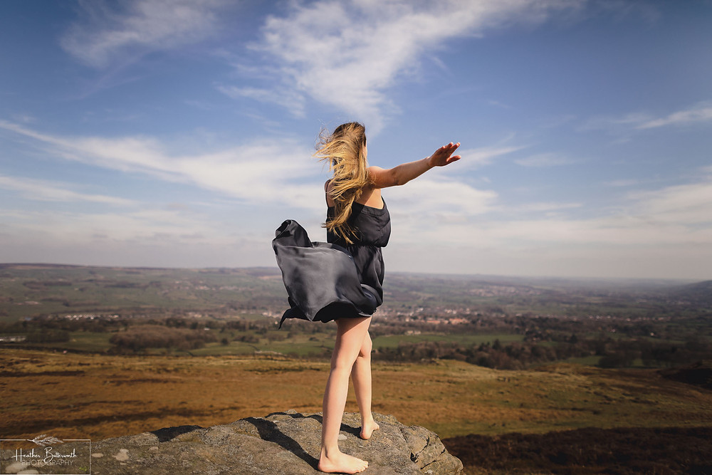 girl in floaty dress on top of a rock on top of burley moor near Ilkley