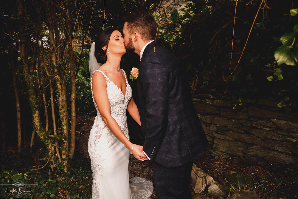 Bride and Groom kissing in the garden at The Burnside Hotel and Spa in Bowness-on-Windermere