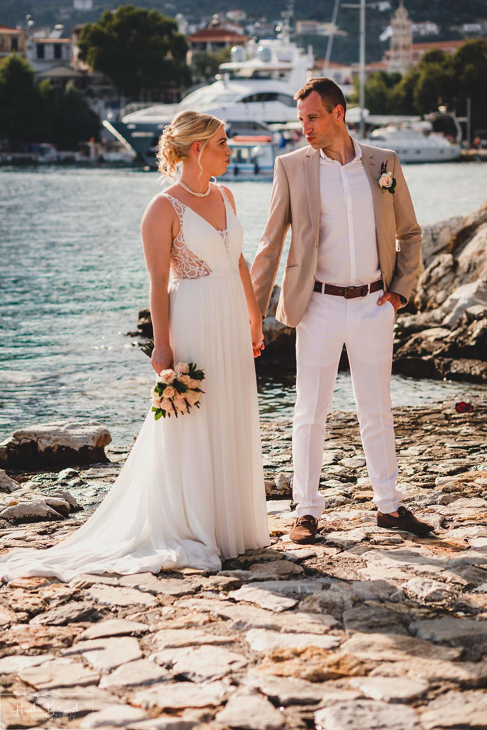 bride and groom holding hands and outing at each other on the beach in skiathos