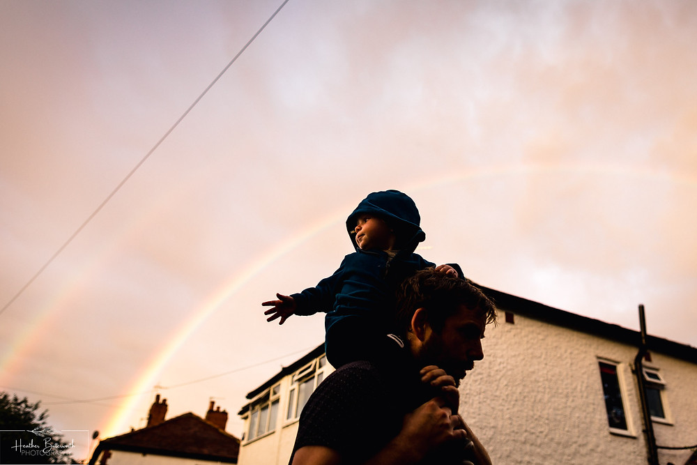 family portrait of a father and son with a rainbow background