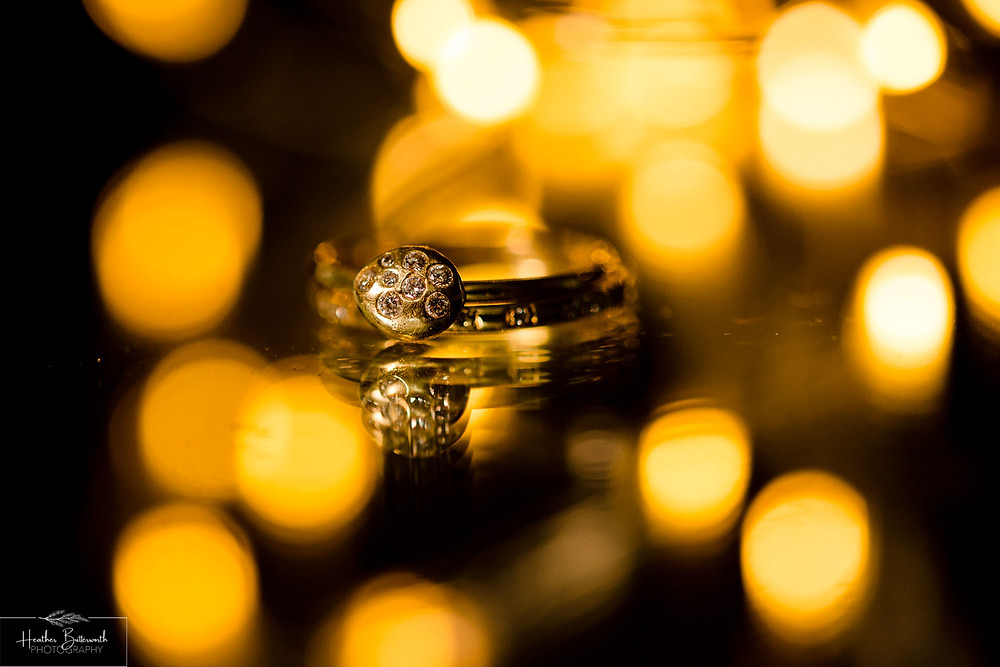 Macro image of gold rings under a light by Heather Butterworth Photography