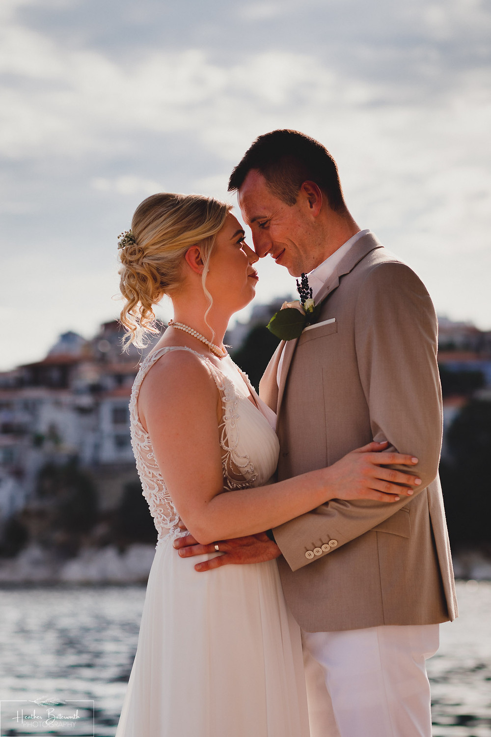 Bride and groom with the sea behind them on the beach together after their wedding at The Bourtzi in Skiathos Town, Greece