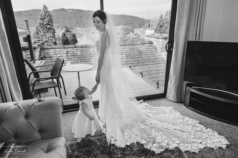 Bride Bex with her baby daughter stood by a window in monochrome during bridal preparations at The Burnside Hotel and Spa in Bowness-on-Windermere