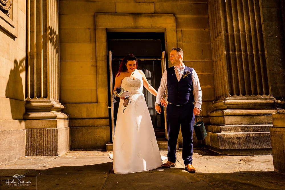 bride and groom holding hands after their wedding at leeds town hall in august 2020