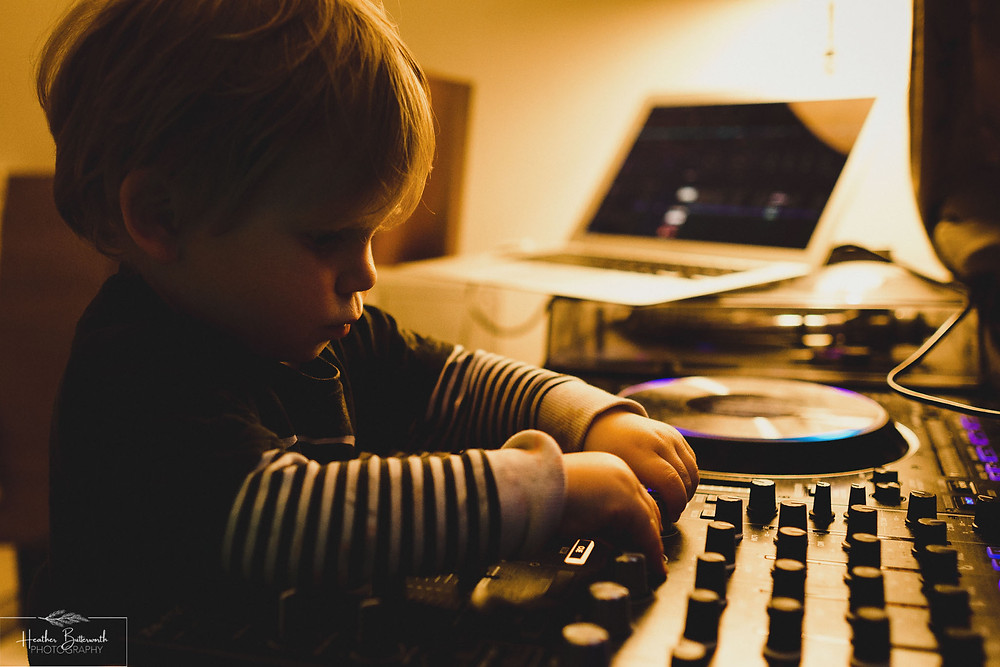 toddler playing with DJ equipment back light with warm light