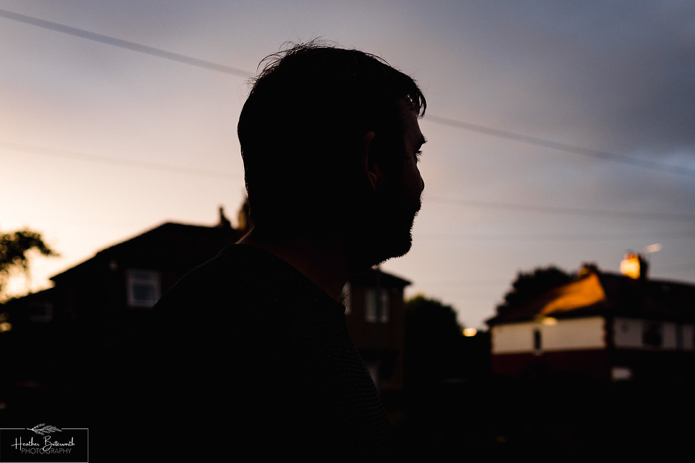 man looking out at dusk down his street in Leeds Yorkshire 2020