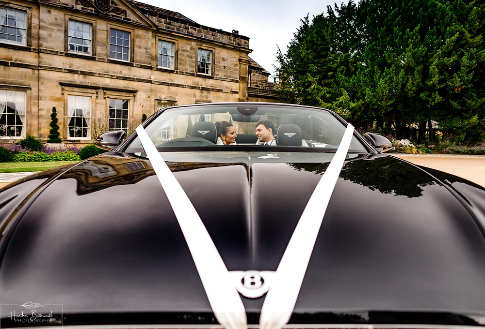 A bride and groom in their Bentley GT Convertible outside Grantley Hall, Yorkshire in July 2020