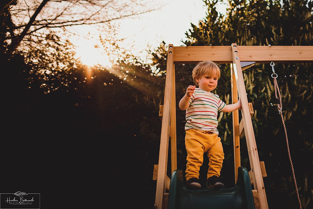 Barney playing on the slide in his family garden in Leeds, Yorkshire. Image by Heather Butterworth Photography