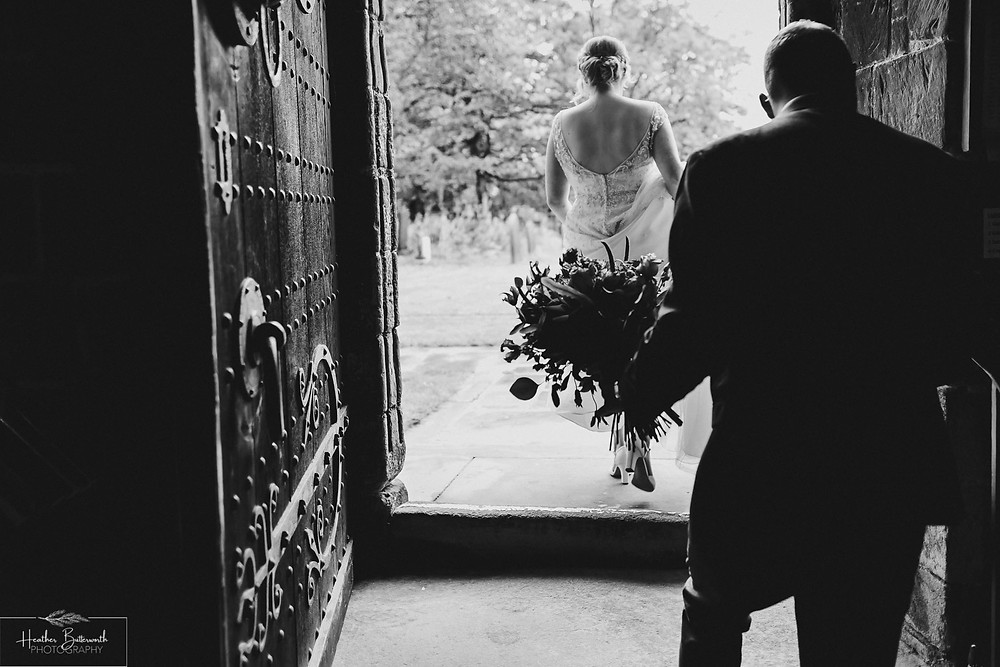 Bride and groom leaving the church after their wedding at Adel Parish Church in Leeds, Yorkshire