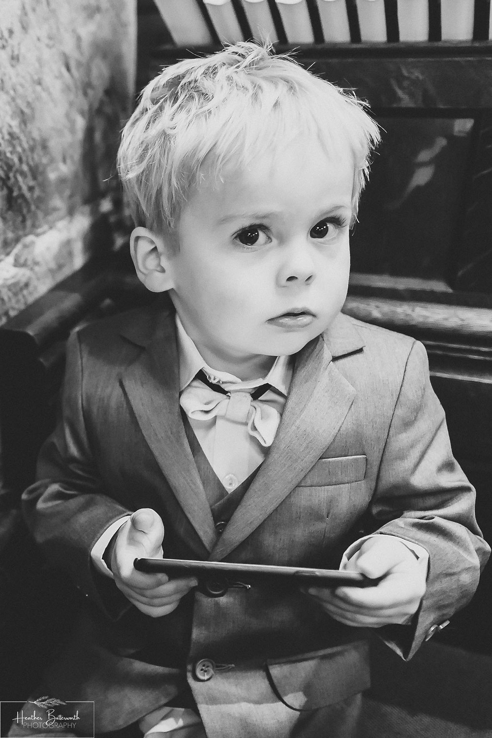 Page boy on caught on a mobile phone after the wedding at Adel Parish Church in Leeds, Yorkshire