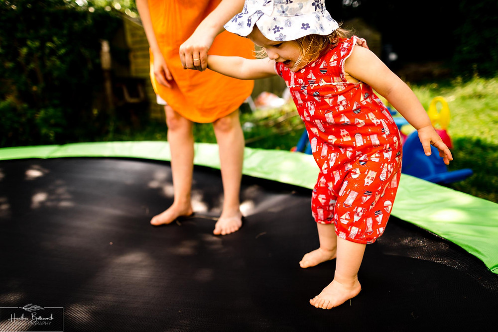 mother and daughter playing together on a trampoline