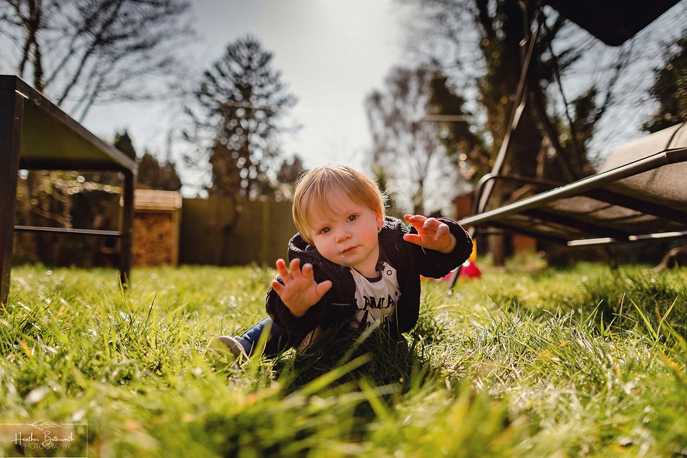 toddler sat on the floor in the garden with the sun behind him reaching out