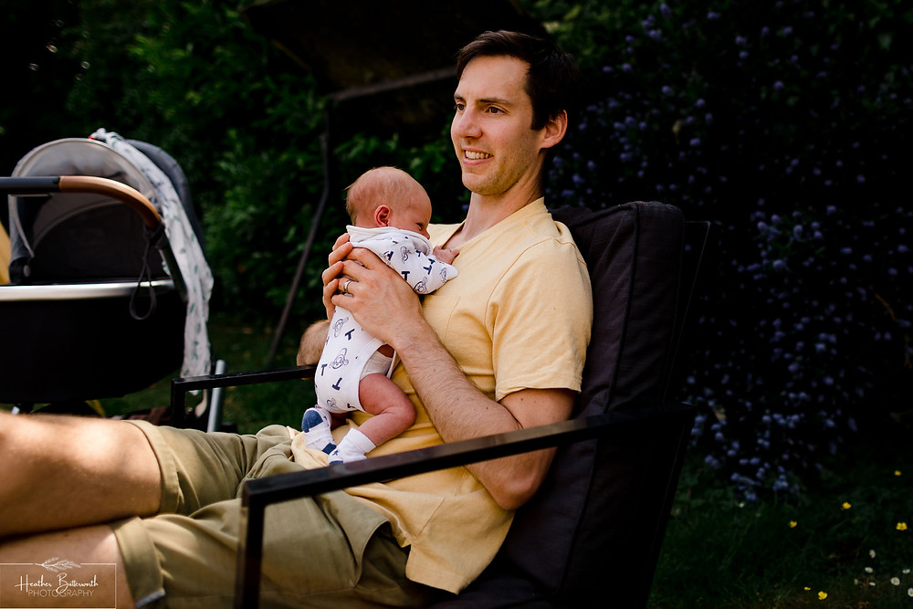 a newborn being held by his happy dad in the garden