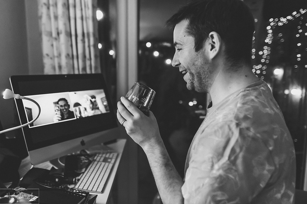 a man having a video call with his friend while enjoying a glass of beer