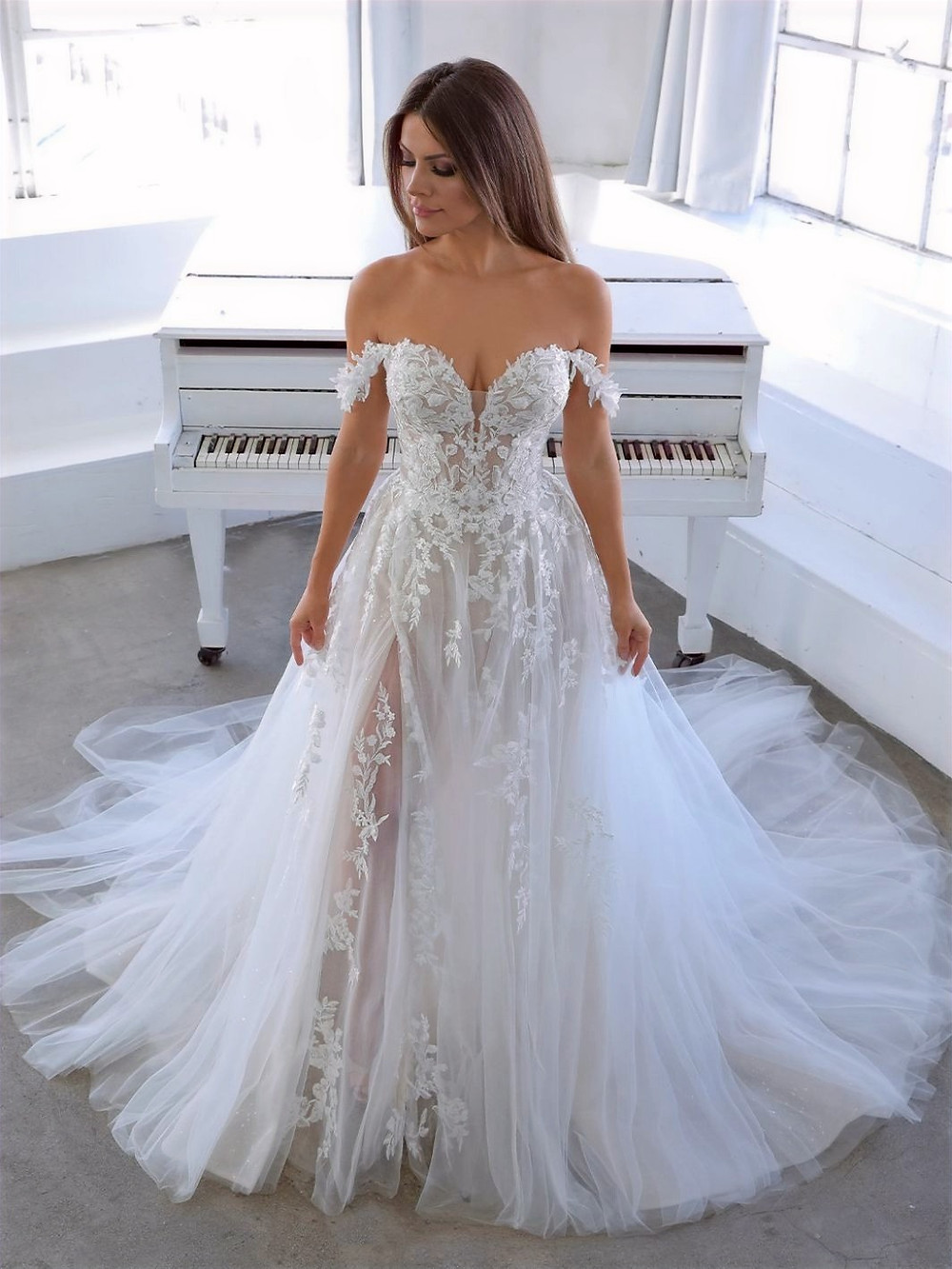 model wearing a wedding dress in front of a piano