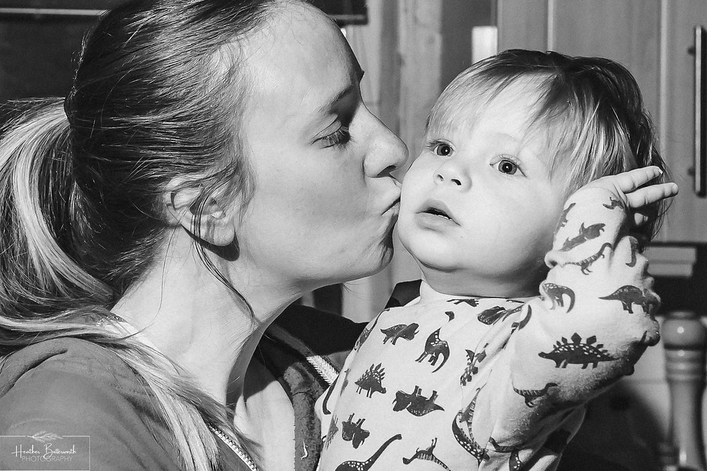 black and white image of a mum kissing her baby on the cheek as he leans backwards with his hand on his ear