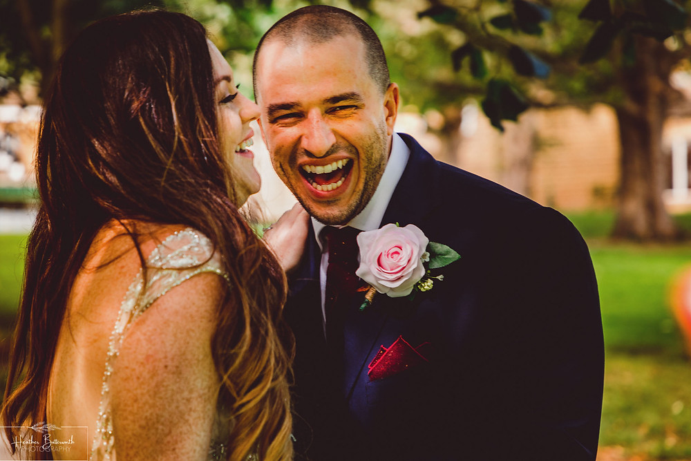 Groom laughing with the bride after their wedding ceremony at Hollins Hall in Baildon, Yorkshire