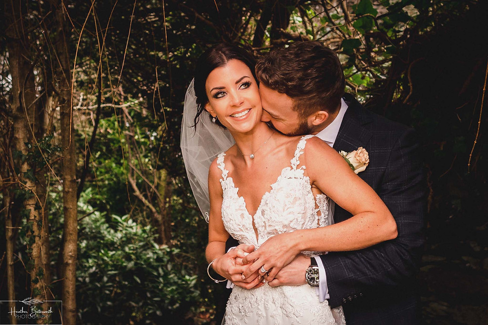 Bride Bex with her new husband Andy in the wooded garden at The Burnside Hotel and Spa in Bowness-on-Windermere