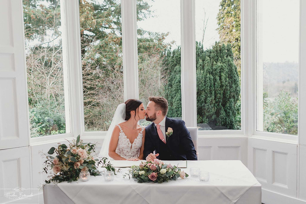 Bride Bex and groom Andy kissing during their ceremony at The Burnside Hotel and Spa in Bowness-on-Windermere