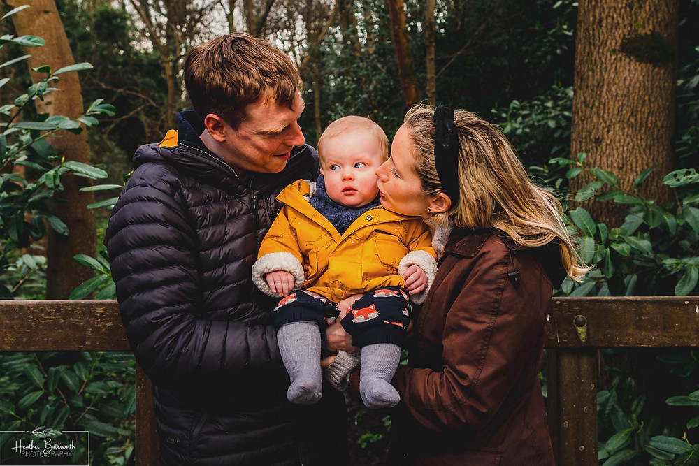 parents holding their toddler son in a wood in roundhay park